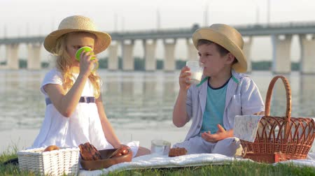 come : lovely hungry kid girl and boy in straw hats eat sweet bakery products and drink fresh milk during picnic in nature near river in sunlight