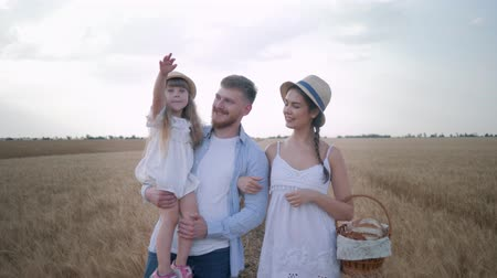 verim : young happy family with little daughter and basket of ruddy bread walking talking laughing and looking away in wheat field Stok Video