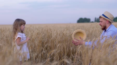 outing : family countryside weekend, young handsome dad and his little sweet girl plays while he shows tricks with straw hat throwing it to each other in harvest seasonal grain wheat field