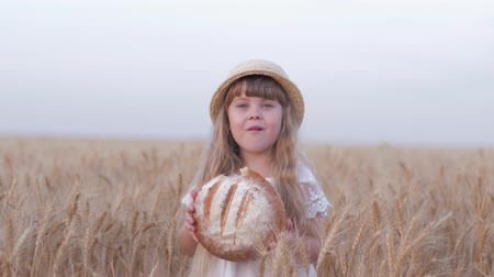 verim : harvesting, small fair kid girl bites tasty baked bread and smiles during outings in golden harvest grain wheat field against sky