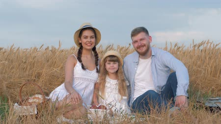 verim : happy young family, cheerful parents with little cute child girl hug and look at each other smiling and sitting at outing in grain harvest autumn barley field shining by sun Stok Video