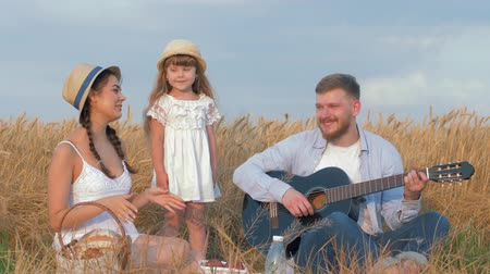 корзина : cheerful family outings, father plays string musical instrument while mom claps her hands and little sweet daughter dances in yield seasonal bread field Стоковые видеозаписи