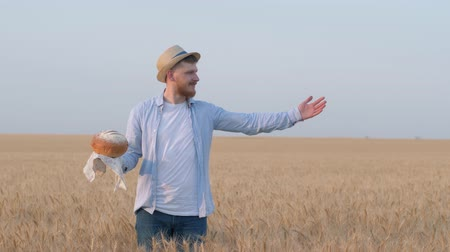 verim : harvesting, happy guy holds bread in his hand and shows with hand expanse of grain wheat field in yield autumn season against sky