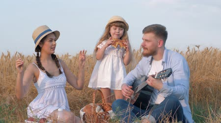 girl claps : family countryside recreation, young dad plays guitar when his woman in straw hat and white dress dances clapping hands and snapping fingers while their little girl kid eating sweet bun in golden grain field picnic