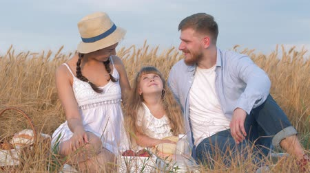amadurecida : happy family portrait, young couple sits together close to their child girl daughter in open air outings in harvest field of matured grain wheat spikes against sky