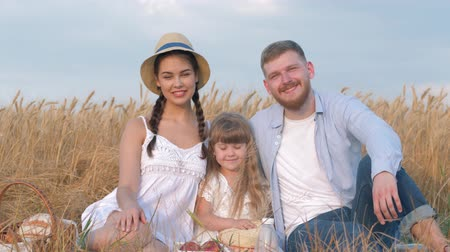verim : idyllic family portrait, happy young couple sits close to their daughter and looks to each other smiling in outdoor picnic in reaped grain barley field at crop time against sky