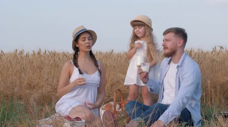 omini : weekend family picnic, happy young mother looks and points towards side talking to husband and little daughter during outings with baked buns and milk in grain wheat meadow at harvesting against autumn sky