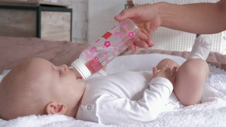 a small bottle : baby drinks water from a bottle that mother holds in her hands, little girl is lying on the bed close-up