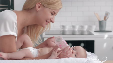 a small bottle : caring mother gives to drink water from the bottle to her newborn girl on the changing table on the kitchen then kisses hands of little baby. Stock Footage