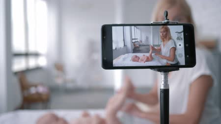 subscriber : maternal care, blogger mom teaches how to change a diaper child girl lying on a changing table while recording training video on mobile phone Stock Footage