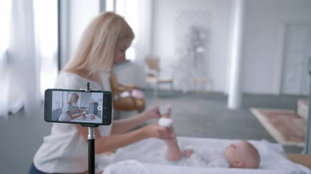 subscriber : video shooting of blog, young mother uses a smartphone and teaches how to do exercises for a newborn baby on a changing table