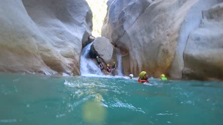quadrilha : BELDIBI, TURKEY - AUGUST 03, 2019: extreme tour, group of tourists into special clothes for safety in unusual place swimming in water and relaxing at waterfall in middle of cliff during traveling
