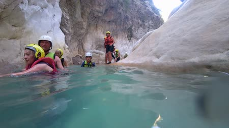 plunging : BELDIBI, TURKEY - AUGUST 03, 2019: extreme tourism, company of tourists with children on active weekends in special costumes swim in water cave against large stones choosing extreme active holidays