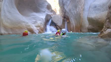 bounce : BELDIBI, TURKEY - AUGUST 03, 2019: extreme vacation with child, active swimming of son and mother tourists in life jackets in underwater cave on background of rock large stones during active vacations