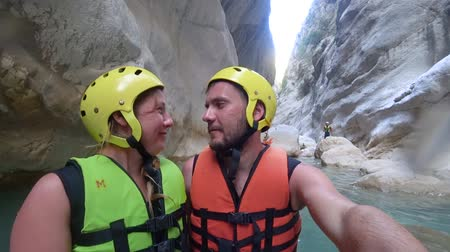 entusiasmo : KHERSON, UKRAINE - AUGUST 03, 2019: honeymoon in an extreme tour, portrait of funny lovers dressed into protective helmets in water lagoon cutely flirt on background of large stones in extremal cave Stock Footage