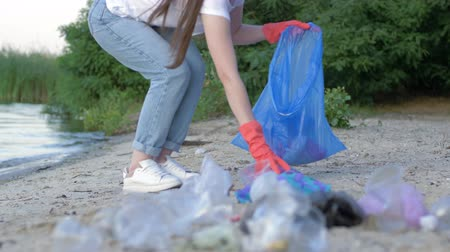 voluntário : beach cleaning, activist female in rubber gloves collects plastic refuse in garbage bag while cleaning embankment close up