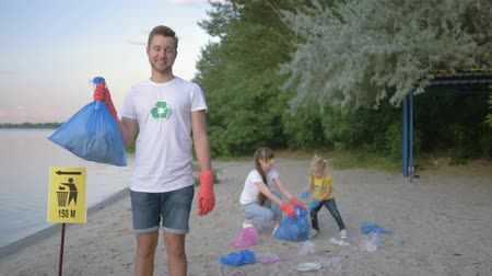 voluntário : care nature ecology, portrait of smiling volunteer guy in rubber gloves with garbage bag near pointer sign on background family with small child collecting plastic trash on dirty beach