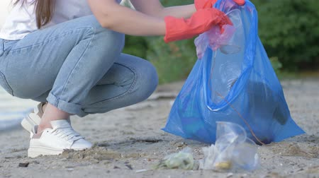 voluntário : care nature ecology, volunteer girl in rubber gloves collects plastic rubbish in garbage bag while cleaning waterfront close up