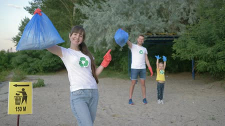 voluntário : cleaning beach, portrait of young volunteer mother in rubber gloves with garbage bag near pointer sign on background father and little daughter after collecting plastic dregs on nature Stock Footage
