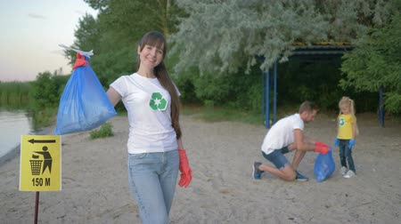 wijzer : cleaning beach, portrait of young volunteer mother in rubber gloves with garbage bag near pointer sign on background father with little daughter collecting plastic dregs on dirty beach