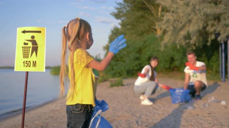 voluntário : cleaning coast, portrait of little happy volunteer girl in rubber gloves with trash bag near pointer sign on background of parents collecting plastic garbage on river beach