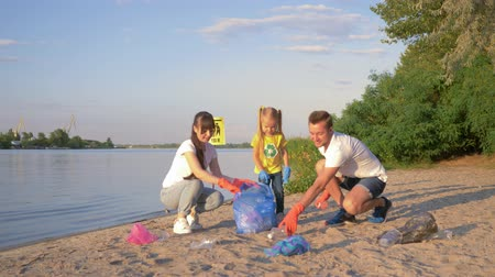 voluntário : cleaning nature, young family of volunteers with child collects garbage in trash bag while cleaning beach from plastic near river Stock Footage