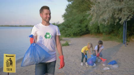 voluntário : ecological situation, portrait of young volunteer man in rubber gloves with garbage bag near pointer sign on background female with kid girl collecting plastic rubbish on dirty beach Stock Footage