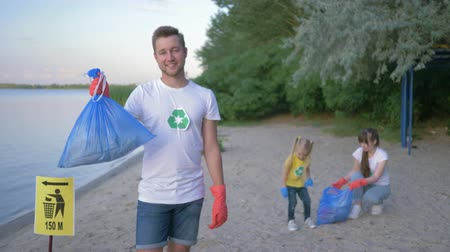 wijzer : ecology rescue, portrait of smiling activist man in rubber gloves with garbage bag near pointer sign on background wife with little daughter collecting plastic and polyethylene litter on embankment