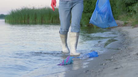 voluntário : environmental problems, young activist girl into rubber boots cleans waterfront from plastic rubbish and collects polyethylene trash in garbage bag while standing in river