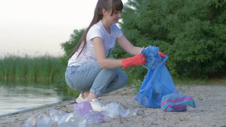 voluntário : environmental protection, activist woman in rubber gloves collects plastic litter in garbage bag while cleaning shore close up Stock Footage