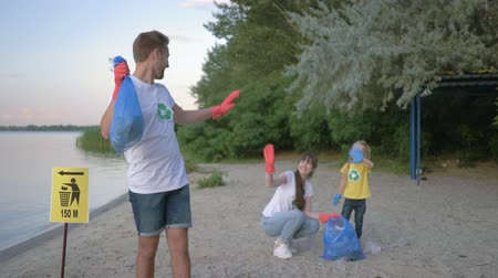 wijzer : environmental protection, portrait of happy volunteer male in rubber gloves with garbage bag near pointer sign on background woman with child girl collecting plastic and polyethylene refuse on beach