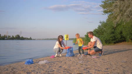 activist : family of volunteers, young father and mother with little daughter collects refuse in garbage bag on dirty beach from plastic and polyethylene while cleaning near river