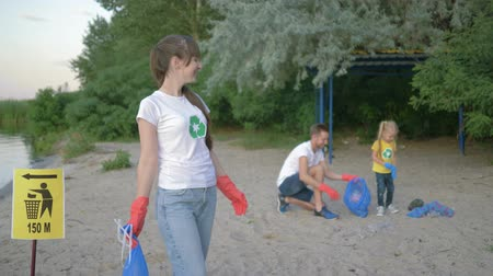 wijzer : picking garbage, portrait of young volunteer mom in rubber gloves with trash bag near pointer sign on background dad with little daughter collecting plastic rubbish on dirty beach Stockvideo
