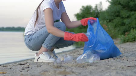 voluntário : picking garbage, volunteer woman in rubber gloves collects plastic and polyethylene trash in refuse bag while cleaning coast close up Stock Footage
