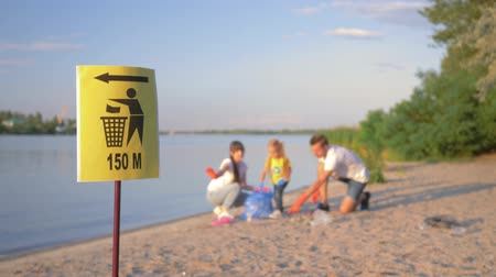voluntário : pointer sign on trash can, young family with little child collects refuse in garbage bag on dirty beach from plastic and polyethylene while cleaning near river in unfocused background Stock Footage