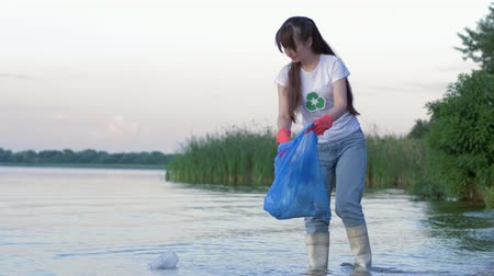 voluntário : problem of plastic pollution, young volunteer woman into rubber boots cleans beach from refuse and collects polyethylene trash in garbage bag while standing in river water