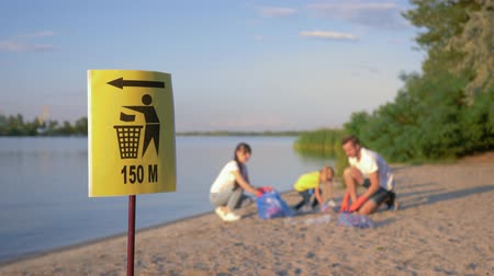 catástrofe : signpost on trash can, young family with little child collects refuse in garbage bag on dirty beach from plastic and polyethylene while cleaning near river in unfocused background