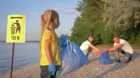 voluntário : stop plastic, portrait of happy volunteer child girl in rubber gloves with trash bag near pointer sign on background of family collecting polyethylene garbage on river beach Stock Footage