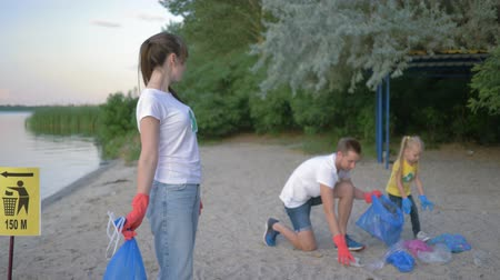 wijzer : stop pollution, portrait of lovely volunteer girl in rubber gloves with trash bag near pointer sign on background guy with kid girl collecting polyethylene refuse on dirty shore
