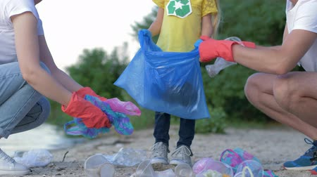 voluntário : young family with little child in rubber gloves collects trash in garbage bag on dirty beach from plastic and polyethylene while cleaning close-up on sand Stock Footage