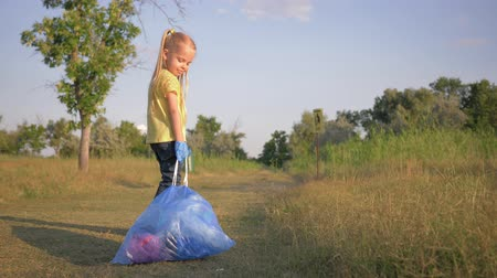 wijzer : care nature ecology, lovely kid girl pulls a big garbage bag with trash on road according to pointer sign to trashcan on open air