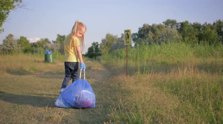 wijzer : children against ecology pollution, cute child girl pulls a big garbage bag with refuse on road according to pointer sign to trashcan outdoors Stockvideo