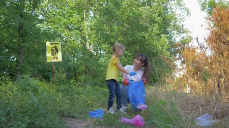 wijzer : ecological care, little child girl helps mom to collect plastic and polyethylene litter in garbage bag while cleaning nature near pointer sign in green grass outdoors