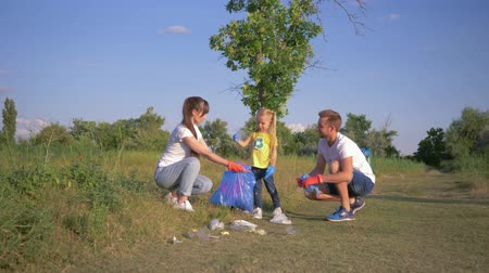 activist : save planet, young family with child girl cares about ecology environmental and collect plastic refuse in trash bag during cleaning from pollution outdoors Stock Footage
