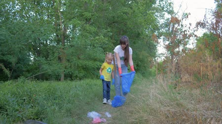 wijzer : society against pollution, little girl helps woman to collect plastic and polyethylene refuse in garbage bag while cleaning nature near pointer sign in green grass outdoors Stockvideo