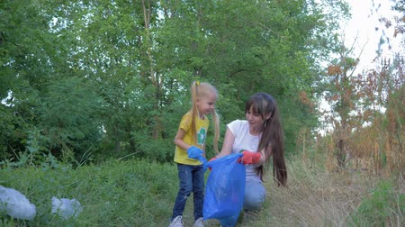 wijzer : stop pollution, little daughter helps mother in rubber gloves to collect plastic and polyethylene rubbish in garbage bag while cleaning nature near pointer sign in green grass outdoors Stockvideo