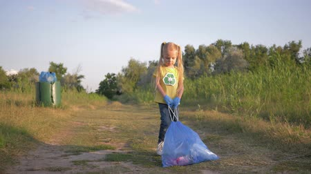 wijzer : stop pollution, sweet child girl pulls a big trash bag with litter on road according to pointer sign to trashcan outdoors