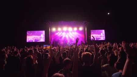 searchlight : KHERSON, UKRAINE - JULY 13, 2019: live music, lot admirers jump to rhythm and clap hands over heads while enjoying rock concert against brightly lit scene with large screens at night