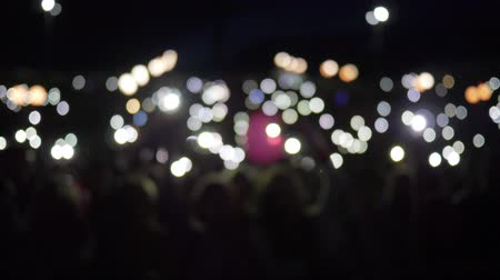 прожектор : arms of fans with mobile phone with burning lanterns waving at rock festival at night in unfocused