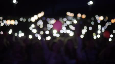 прожектор : hands of fans with smartphone with burning lanterns waving at night rock concert In dark in unfocused